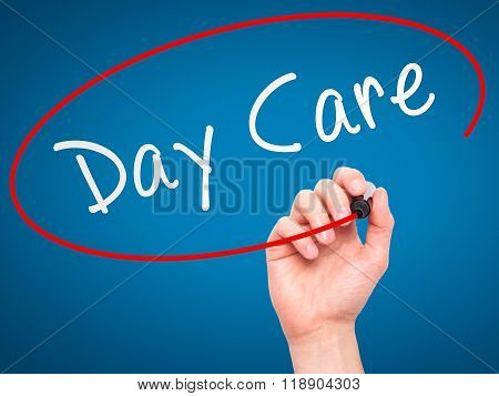 Man Hand Writing Day Care With Marker On Transparent Wipe Board Isolated On Blue