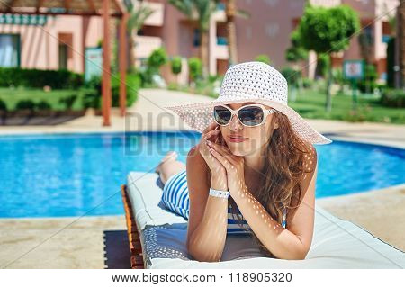 Beautiful woman in a big white hat on lounger by the pool