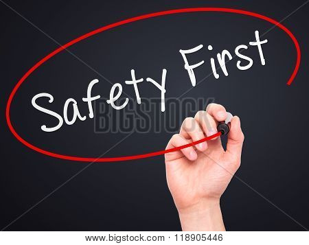 Man Hand Writing Safety First With Marker On Transparent Wipe Board
