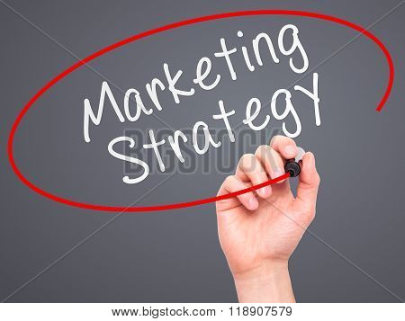 Man Hand Writing Marketing Strategy With Marker On Transparent Wipe Board