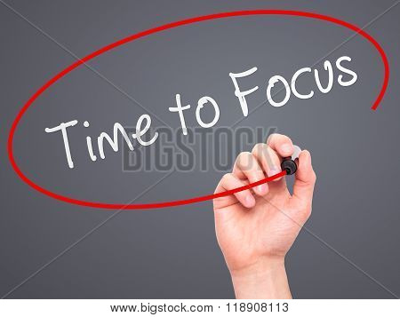 Man Hand Writing Time To Focus With Marker On Transparent Wipe Board
