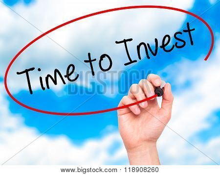 Man Hand Writing Time To Invest With Marker On Transparent Wipe Board