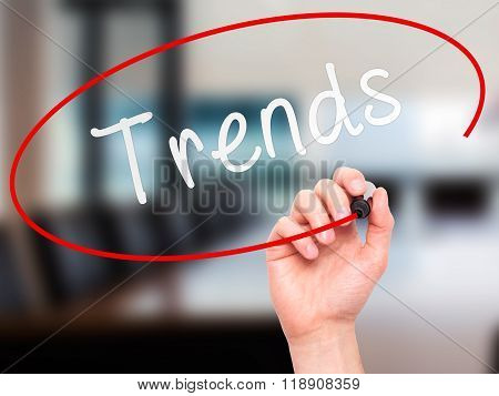 Man Hand Writing Trends With Marker On Transparent Wipe Board