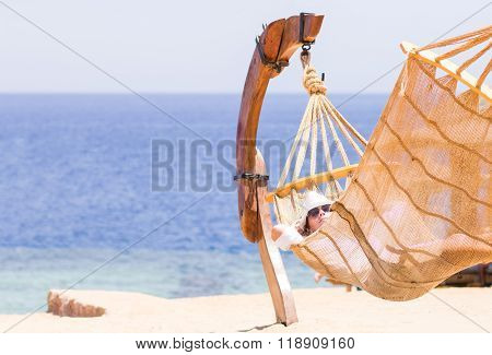 Young Woman Resting In Hammock Near The Sea