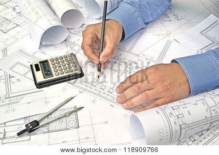 Hands with tool and project drawings