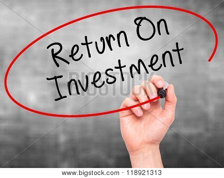 Man Hand Writing Return On Investment  With Black Marker On Visual Screen