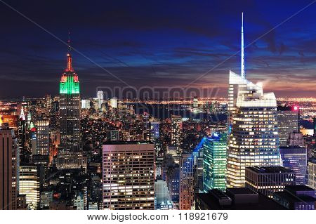 New York City skyline aerial view at night with colorful cloud, Empire State Building, and skyscrapers of midtown Manhattan.