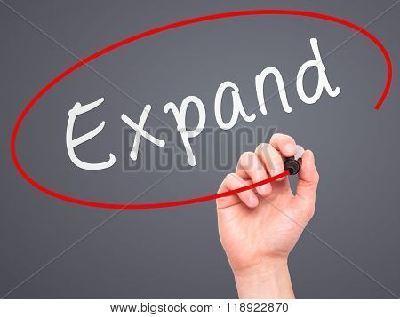Man Hand Writing Expand With Marker On Transparent Wipe Board