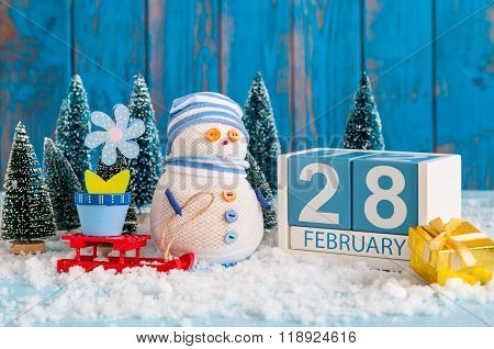 February 28th. Cube calendar for february 28 on wooden surface with snowman, sled, snow, fir and spr