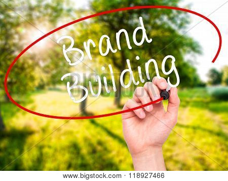 Man Hand Writing Brand Building With Black Marker On Visual Screen