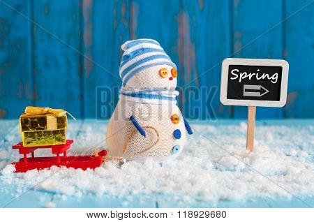 Spring change winter background. Snowman with gift and red sled stand near direction sign spring. Po