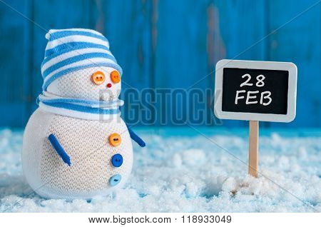 February 28th. Snowman near direction sign 28 feb. Concept of winter end