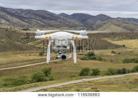 FORT COLLINS, CO, USA, SEPTEMBER 11, 2015:  Radio controlled Phantom 3 quadcopter drone is flying with a camera over foothills of Rocky Mountains.