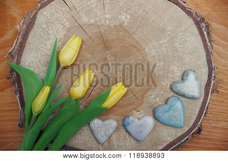 Rustic Wooden Background With Tree Slice, Tulips And Stone Hearts