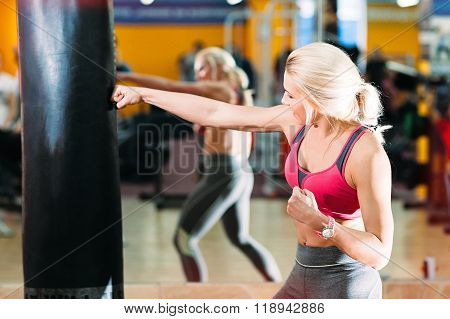 athlete strongly hits punching bag.