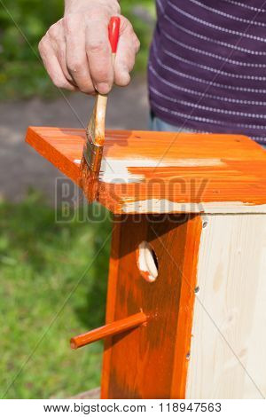 Adding Red Protective Covering With Brush On Birdhouse