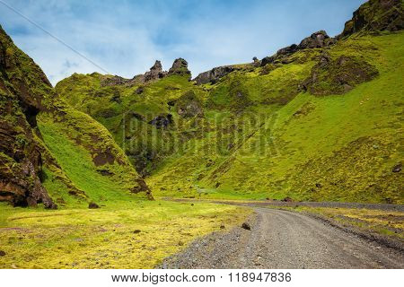 The summer blossoming Iceland. A canyon Pakgil - green grass and moss on fantastic rocks. On canyon there is dirt road