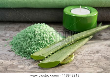 Green fresh leaves of aloe vera, candles, aloe bath salt, towels