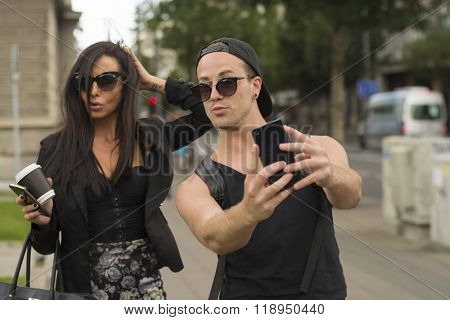 Two cheerful friends taking photos of themselves on smart phone, urban city outdoor scene, selective focus