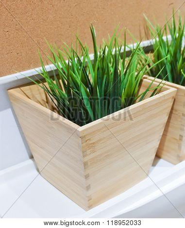 Green Artificial Plant In A Wooden Pot
