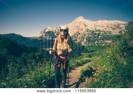 Girl Traveler hiking mountains landscape on background