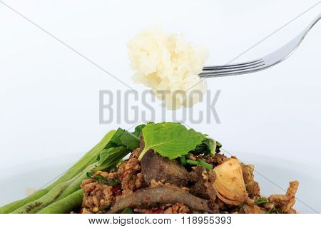 Thai ground pork salad, Spicy minced pork and pork liver salad with sticky rice on fork (Larb Mu)