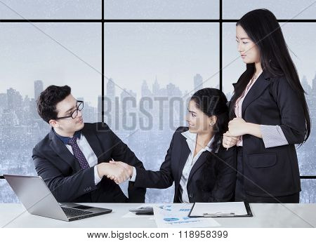 Mixed Race Entrepreneurs Shaking Hands In Office