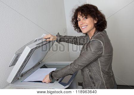 Pretty Smiling Secretary Using A Copy Machine At Work