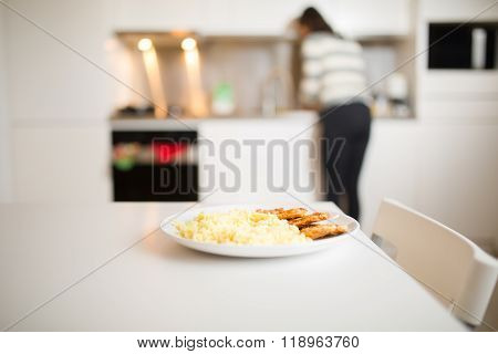 Chicken and rice on a plate, healthy nutrition fitness diet food and woman in the background cooking at home. Single person cooking dinner for one alone. ** Note: Shallow depth of field