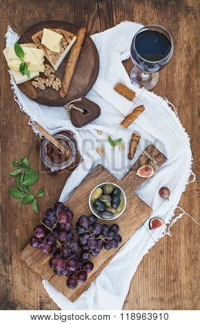 Glass of red wine, cheese board, grapes, walnuts, olives, honey and bread sticks on rustic wooden ta