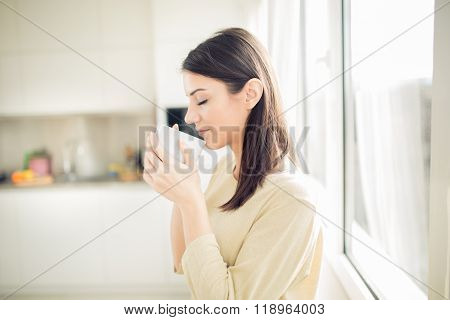 Young woman enjoying,holding cup of hot beverage,coffee or tea in morning sunlight.Enjoying morning