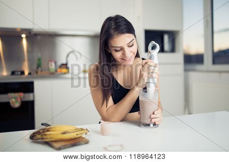 Woman with hand blender making sweet banana chocolate protein powder milkshake smoothie
