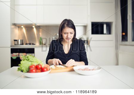 Young housewife beginner cook crying while cutting onion.Slice,dice and chop onion