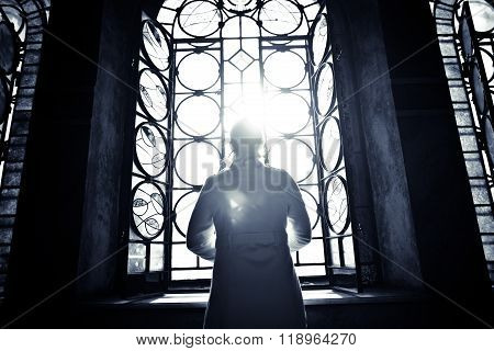 Religious christian woman looking trough the stained glass church window light.Woman praying to god