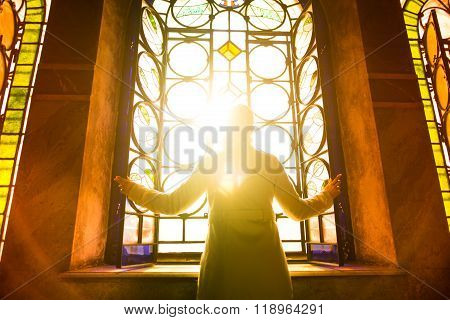 Religious christian woman looking trough the stained glass church window light