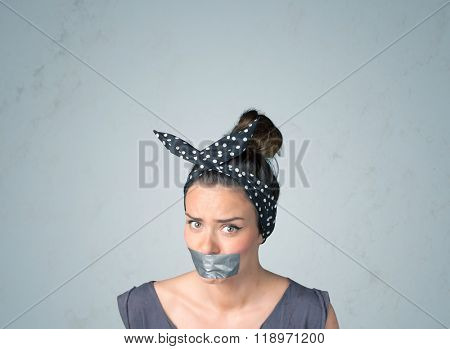 Young woman with taped mouth. Isolated on the gray background