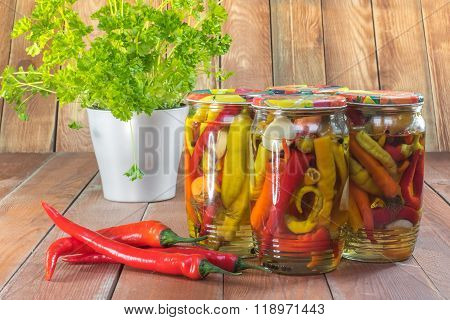 Pickled Chilli Peppers In Glass Jar With Fresh Chilli And Parsley