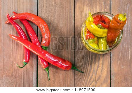 Top View On One Open Pickled Chilli Peppers In Glass Jar With Fresh Chilli