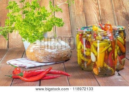 Pickled Chilli Peppers In Glass Jar With Fresh Chilli, Bread And Parsley