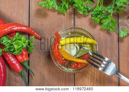 Top View On Preserved Pickled Chilli Peppers In Glass Bowl With Fork, Fresh Chilli And Parsley