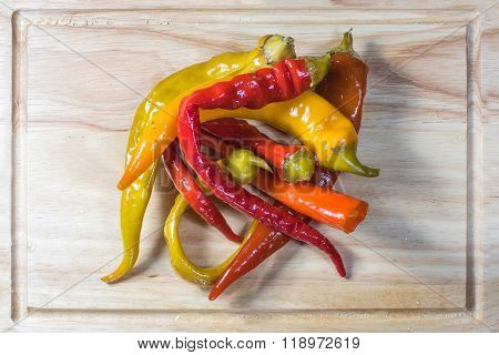 Top View On Preserved Pickled Chilli Peppers On A Chopping Board