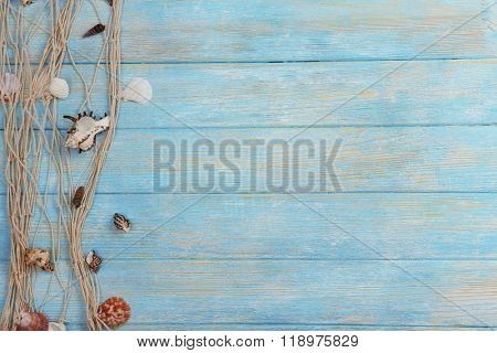 Seashells and fishing net on wooden background