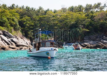PHI PHI ISLANDS, THAILAND - CIRCA FEBRUARY, 2015: Small cruise boats with tourists on the shore of the island of Phi Phi in Andaman Sea. Island is very popular with tourists from all over the world