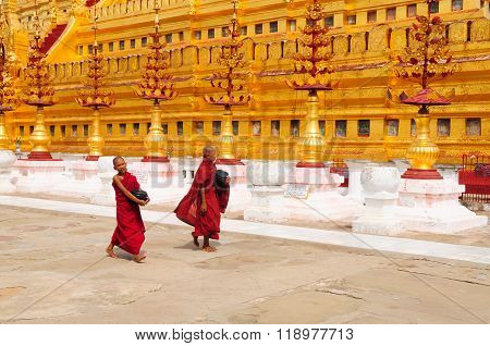 Two unidentified Buddhist novices are in Shwezigon Pagoda in Bagan, Myanmar.
