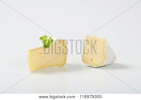 two slices of white rind cheese with parsley on white background