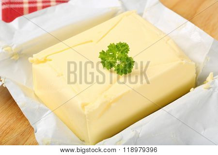 block of fresh butter on wooden cutting board - detail