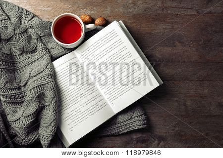 An open book, a cup of tea and a blanket on the wooden background
