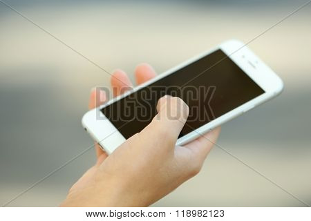 A female hand holding a mobile phone outdoors, on blurred background