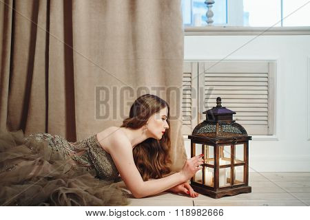 Woman In Elegant Dress Looking In Lantern