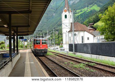 FLUELEN, SWITZERLAND - JULY 4, 2014: Train Platform. A train comes in at the platform in Fluelen, Switzerland, on Lake Lucerne.